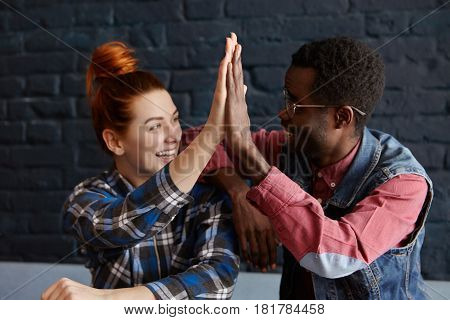 Cheerful Young Redhead Caucasian Female And Stylish Afro-american Male In Glasses And Hat Giving Hig
