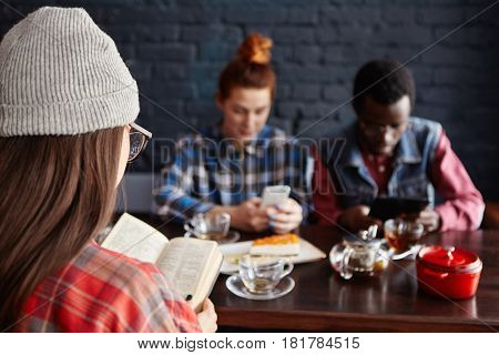 Multiethnic Group Of Stylish Young Students Drinking Tea At Cafe During Break: Girl In Hat Reading B