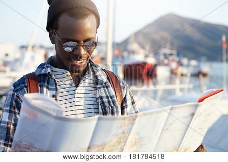 Happy Excited Dark-skinned Man Traveler Wearing Stylish Clothing Holding City Guide In His Hands Whi