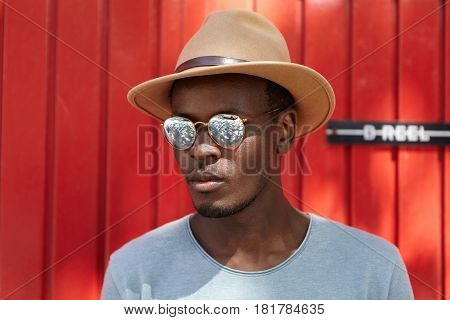 Portrait Of Stylish Handsome Young Afro-american Man With Bristle Standing Outdoors Against Red Wall