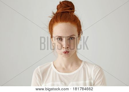 Studio Shot Of Grumpy Stubborn Young Ginger Woman With Hair Knot Blowing Cheeks And Pouting While Fe