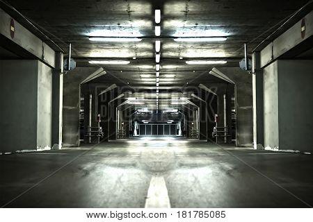 Empty underground parking garage interior. Neon lights at night.