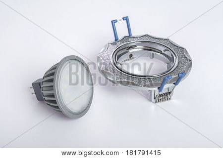 Recessed ceiling light and LED lamp to him on a table on a white background