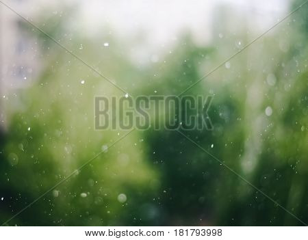 Blurry raindrops on window glass abstract background in spring