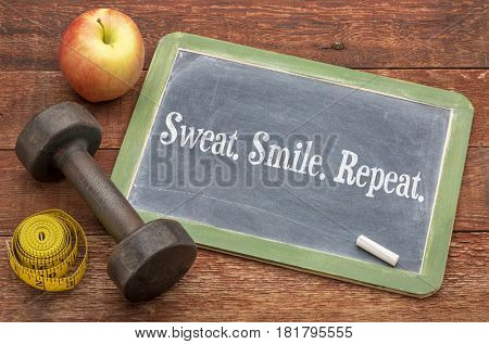sweat, smile, repeat fitness concept -  slate blackboard sign against weathered red painted barn wood with a dumbbell, apple and tape measure