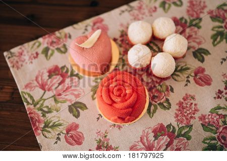 Different cakes on a wooden table and rag napkin in flowers. Red cakes.
