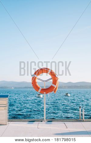 Lifebuoy in the marina for yachts. Red circle on the boat dock. Porto Montenegro, Montenegro.