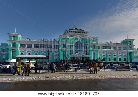 OMSK, RUSSIA - FEBRUARY 14, 2015: People in front of the central train station. The  station was founded in 1896 and then several times enlarged and reconstructed