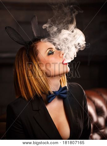 Young attractive girl in a jacket a butterfly tie and bunny ears smokes an electronic cigarette. Femme fatale. Evening makeup smokey eye. She lets out thick steam from her mouth. Pleasure in vice.