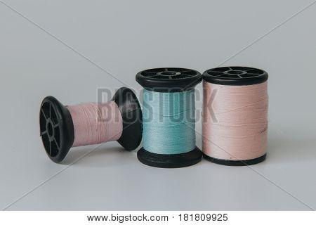 Thread bobbin on white background with vintage filter.