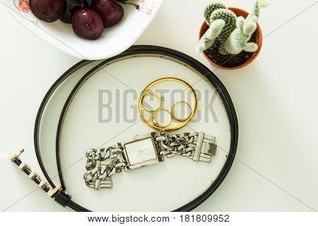 Fashionable female accessories watch glasses belt on table