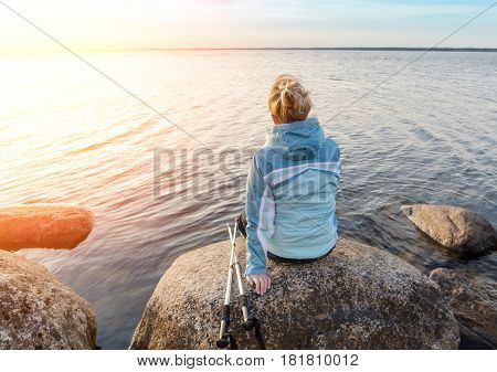 Happy Girl With Hiking Sticks At A Lake On The Rocks. Estonia