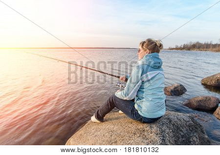 Girl Sitting On A Rock With A Fishing Rod