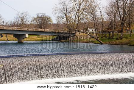 A small man made waterfall under a concrete bridge in a springtime countryside landscape dotted with budding trees and green grass