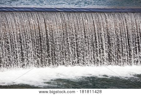 Close up of calm flowing water of a small waterfall cascading over a lip and splashing down churning up foam