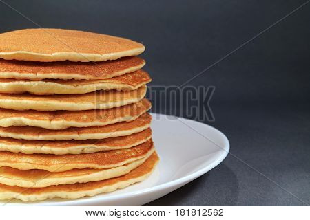 Stack of fresh homemade plain pancakes served on white plate, isolated on black background