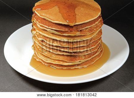 Pile of Fresh Homemade Pancakes Served with Maple Syrup on White Plate, Isolated on Black Background