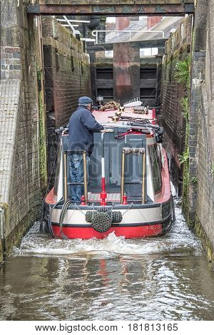 A view from the rear of a narrowboat on a canal negotiating and entering a lock