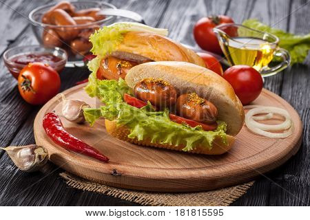 Hot dog with Tomato, lettuce, Sausage, mustard, ketchup on the black wooden table