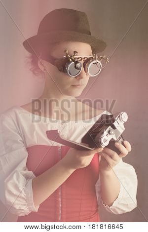Attractive steampunk girl wearing goggles and hat hold old camera