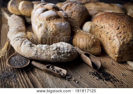 Mixed bread top view shot. Different fresh bread on old wooden table.