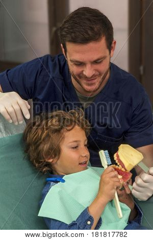 Dentist explaining brushing procedure to a kid using artificial teeth's in clinic