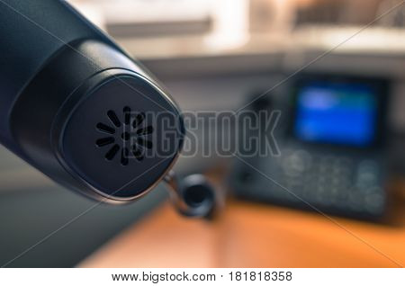 Man holding a black telephone receiver. Close up. Bokeh.