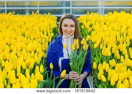 Woman gardener dressed in a working uniform holding in his hands bunch of tulips and smiling looking at the camera while standing in a large garden center. Industrial cultivation of flowers
