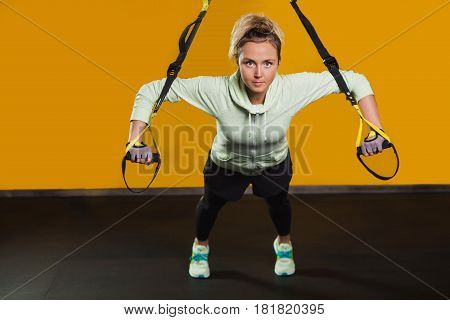 Sporty woman doing hand exercises with suspension straps Looking at camera, at gym. Suspension training for hardy body