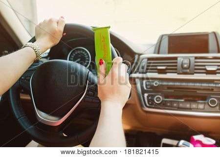 Female hands hold a protein bar, while driving. Out of focus Car dashboard. Healthy and fast food while driving