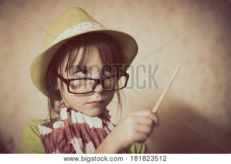 Fashionable little girl with a pencil in hand points to the top.