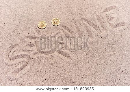 Word sun (Sonne) in german written on the sand of the beach