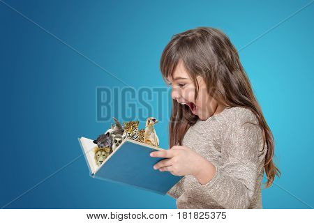 Surprised long haired little girl holding open book in her hands. From the book are protruding animals. All is on the blue gradient background.