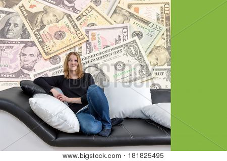 Grinning long haired young woman is sitting on a black and white couch with black and white pillows. Woman is looking upwards on the US dollar bills in the background. Empty trendy green color rectangle is ready for your text.
