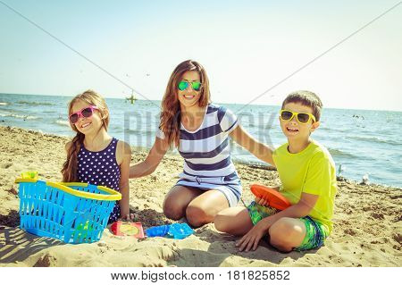 Happy family mother daughter and son having fun on beach sand. Parent mom and children kids with toys at sea. Summer vacation holidays relax and happiness.