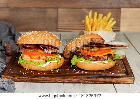 Two cheeseburgers in the decor filmed closeup on wooden background