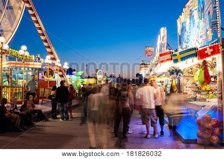 Altoetting,Germany-June 13,2009: The lights of the ride and food stalls iluminate people as they walk around and enjoy a warm evening at the local fair in this long exposure