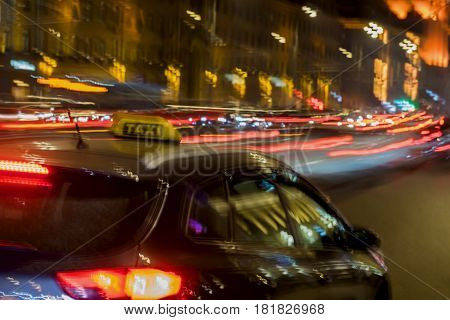 Abstract vintage tone motion, blurred image of taxi, night urban street traffic and bright city lights with bokeh lights, for background use
