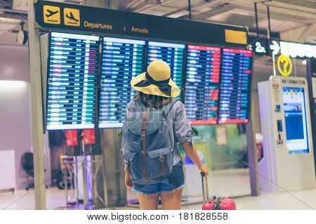 Young woman traveler in international airport looking at the flight information board holding suitcase or baggage in her hand checking her flight at the airport terminal.