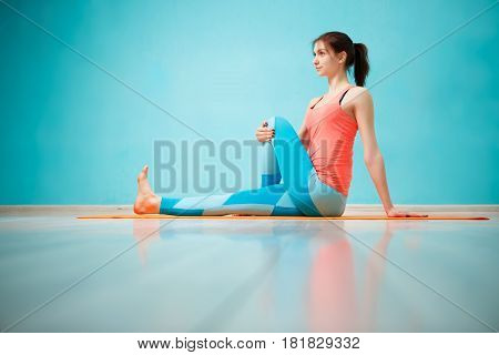 Photo of sportswoman practicing yoga on rug