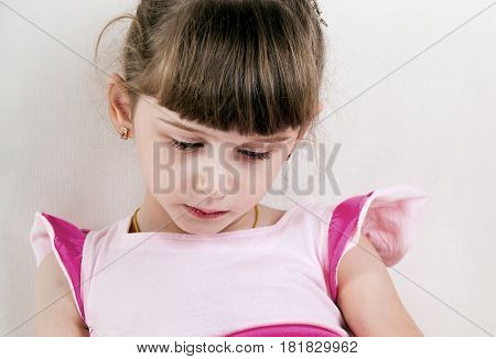 Sad Small Girl on the White Wall Background