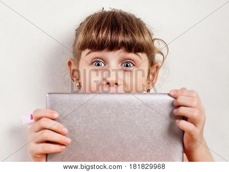 Surprised Small Girl with Tablet Computer on the White Wall Background