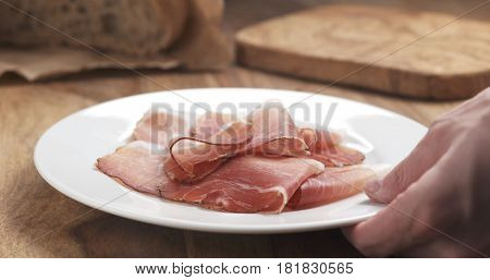 Italian speck ham on a plate put on table, 4k photo