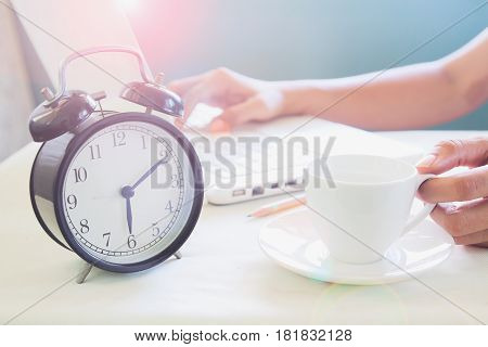 Woman working on laptop computer and drinking coffee on modern white working space with classic alarmclock