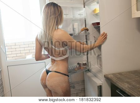 woman searching food in the fridge showing her ass and legs. Big sexy buttocks.