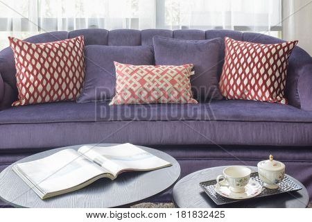 Magazine And Afternoon Tae Set On Center Table With Violet Sofa In Background