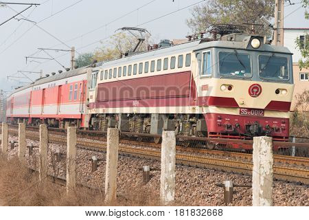 HENAN CHINA - NOV 19 2014: China Railways SS7C electric locomotive in Luoyang Henan China. The locomotive is hauling passenger car.