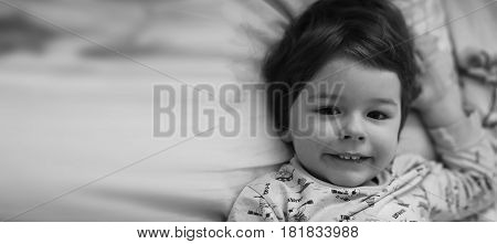Black and white photo portrait of a young child lying on pillow
