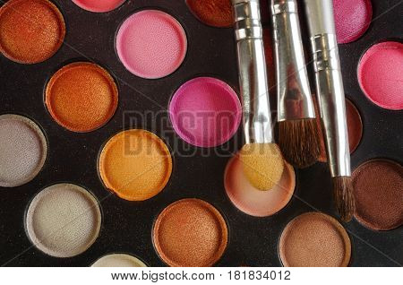 Three Brushes on the palette of eye shadows - pink, orange, brown, golden and nude colors