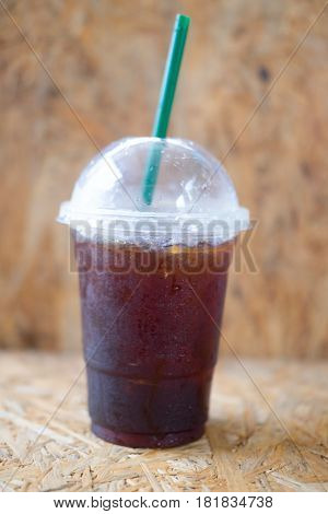 Plastic cup of iced black coffee americano on wood table